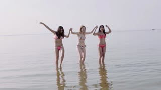 Group of mixed race girls running on the beach and smiling, in a stylish bikini enjoying summer vacation