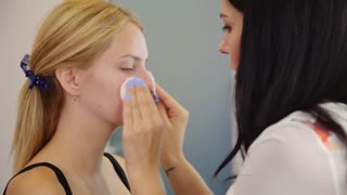 Make-up artist cleaning skin on model's face. Concept of skin care