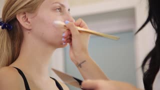 Makeup artist applying liquid tonal foundation on the face of the pretty woman in make up studio. Concept of fashion