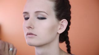 Makeup artist applying professional make up on the face of the beautiful young female model. Orange background