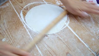 Making bread on wooden table background. Hands only