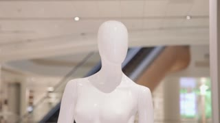 Mannequin or dressmakers dummy on with shopping mall on background. Copy space text