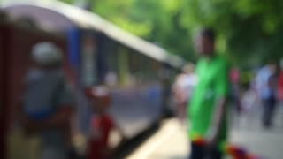 People crowd out of focus at a retro steam train station in the forest.