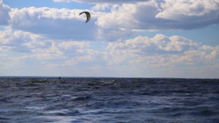 People windsurfing kiteboarding. Static landscape panorama shot with low clouds at sunny weather.