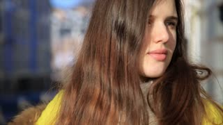 Portrait of beautiful young woman with wind in hair. Pretty brunette female