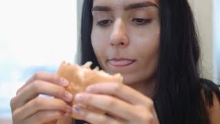 Pretty young latina funny woman eating hamburger indoor. Fast food