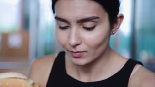 Pretty young latina funny woman eating hamburger outdoor on the street. Fast food