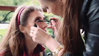 Professional makeup artist applying make up on a beautiful young female model's face outdoor