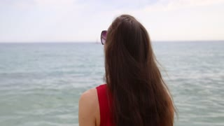 Relaxed girl walking on a beach of Mediterranean Sea and pointing something far at horizon