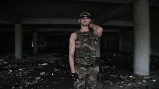 Sexy muscular man dancer in military clothes and dark glasses dances. Shows sports figure. Beautiful male model dance. Long shot take. No colour correction. Color graded version available