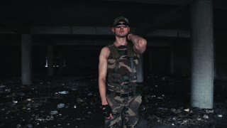 Sexy muscular man dancer in military clothes and dark glasses dances. Shows sports figure. Beautiful male model dance. Long shot take. Professional color correction. Non color corrected version