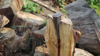 Someone chopping wood with an axe. Firewood in a background.