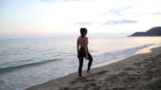 Sport girl making yoga at sunset on the beach of Mediterranean Sea