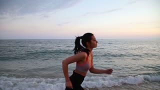 Sport leisure girl running on the beach of Mediterranean Sea at sunset