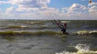 Sporty fit female kiteboarder walking in water with lunched kite and ready to start kiteboarding session.