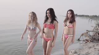 Three young mixed race women with a slender figure run and having fun at sea coast line at sunset. Steadycam stabilized slow motion shot