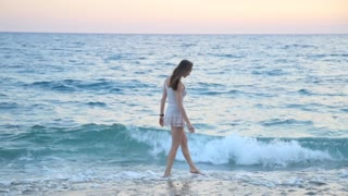 Travel concept. Beautiful girl on the beach alone