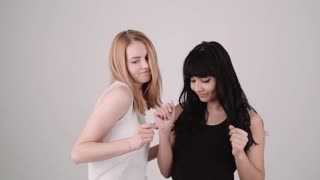 Two happy girls brunette and blonde slowly dancing together indoors on light grey background. Copy space text. Properly color corrected version