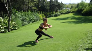Active woman exercising and stretching in city park. Attractive fit girl training squatting at morning outdoors. Healthy, fitness, wellness lifestyle. Sport, cardio, workout concept