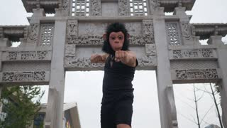 Adult man acting silly funny in monkey mask in front of ancient temple somewhere in asia.