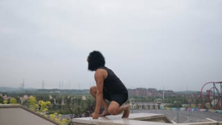 Adult man acting silly funny in monkey mask with cityscape at background in slow motion.