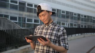 Asian man in city using tablet computer PC outdoors wearing checkerboard shirt