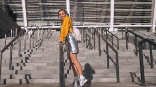 Attractive Cute Young Hipster Millenial Woman Student having Fun Riding a Banister and Listening to Music at Urban Background. Wearing backpack, yellow blouse and silver skirt.