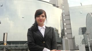 Beautiful smiling business woman standing against office building. Thumbs up