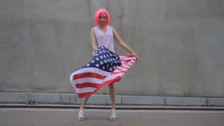 Beautiful young mixed race woman in pink wig with American flag at city street