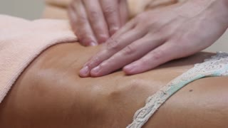 Brunette fit woman client receiving belly body massage at spa club by tattooed massagist