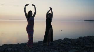 Carefree women in long black dress dancing on beach at sunset.