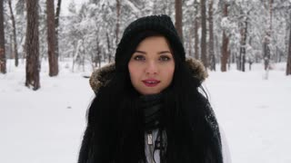 Charming smiling brunette young woman in coat in snowfall in the forest. Expressing positivity, true emotions, enjoy snowing, waiting for christmas holidays