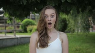 Cinemagraph of pretty cute young woman surprised shocked on green trees background. Real people expression loopable