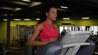 Close up of attractive mixed race woman running on the treadmill in the sport gym in slow motion