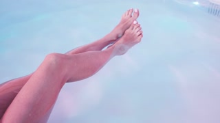 Close up of young woman legs floating in Spa bath or swimming pool, she is very relaxed. Welness concept.