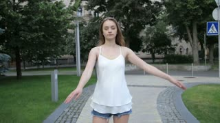Contemporary caucasian ballet street dancer woman urban dancing freestyle in the city