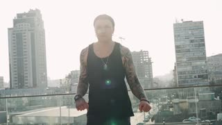 Contemporary hip hop street dancer hipster man with tattoo funky urban dancing freestyle in the city. 4k slow motion