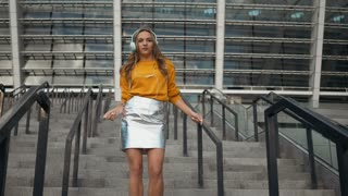 Cute Attractive Woman silly funky dancing freestyle with earphones in urban city streets celebrating achievement success concept.