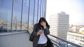 Fashion beautiful hispanic latina woman texting on smartphone walking in the city. Rooftop with cityview at background