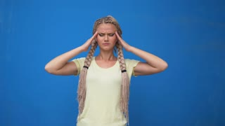 Fatigue stressful young female model keeps hands on head, closes eyes and opens mouth in desperation, has terible headache, isolated over blue background. Tiredness and exasperation concept.