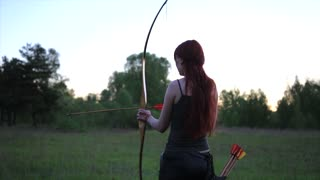 Female ginger hair archer shooting targets with her bow and arrow with self made mehendi henna tatoo on hand. Concentration concept