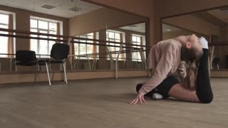 Flexible young woman dancer stretching legs at studio in slow motion