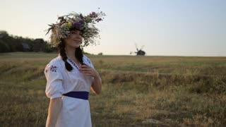 Girl walking in meadow wearing flower circlet and ethnic outfit at sunset in nature