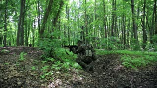 Guerilla partisan warrior aiming in forest ambush carrying his gun. Changing position maneuver. Relocation