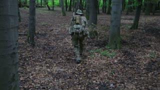 Guerilla partisan warrior aiming in forest ambush carrying his gun. Partisan war reconstruction. War battlefield maneuvers training
