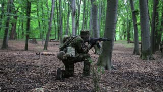 Guerilla partisan warrior aiming in forest ambush carrying his gun. War battlefield maneuvers training