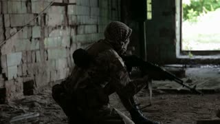 Guerilla partisan warrior operation in urban environment. Soldier aiming an enemy with his gun. War battlefield maneuvers training