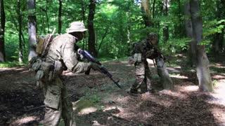 Guerilla partisan warriors attacking aiming in forest ambush carrying their guns. War battlefield maneuvers training. Steadicam shot