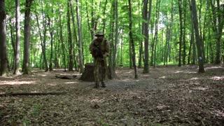 Guerilla partisan warriors attacking aiming in forest ambush carrying their guns. War battlefield maneuvers training