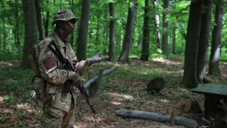 Guerilla warriors squad commander instructing his fighters in the forest bushes. War battlefield maneuvers training